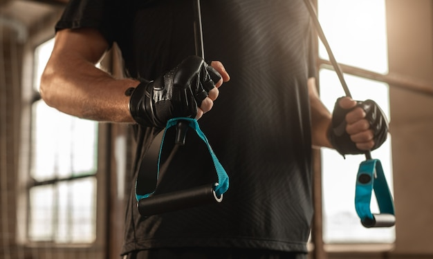 Atleta masculino anônimo em luvas e com corda elástica nos ombros se exercitando em uma academia moderna durante exercícios físicos