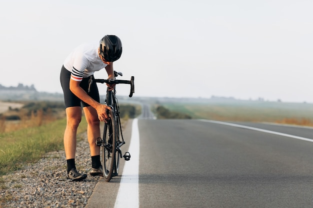 Atleta masculino bonito com capacete protetor e roupas esportivas, verificando as rodas da bicicleta preta