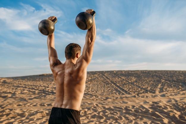 Atleta masculino com dois kettlebells no deserto