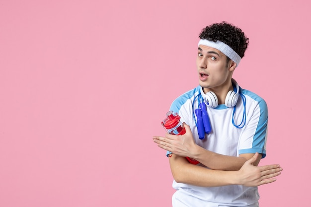 Atleta masculino com roupas esportivas e garrafa de água.