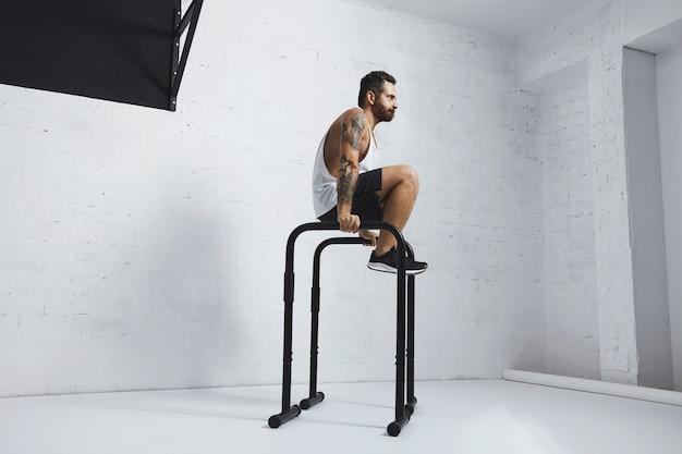 Atleta masculino com tatuagem forte em camiseta branca sem etiqueta sem rótulo mostra movimentos calistênicos chute para fora l sente-se, mova-se ou enfie-se em barras paralelas