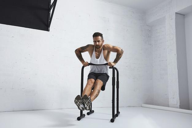 Atleta masculino com tatuagem forte em camiseta branca sem etiqueta sem rótulo mostra movimentos calistênicos mergulhos diretos movem dois, mergulhe em uma das barras paralelas