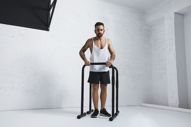Atleta masculino com tatuagem forte em camiseta branca sem etiqueta sem rótulo mostra movimentos calistênicos pernas estendidas e flexões de braço em barras paralelas