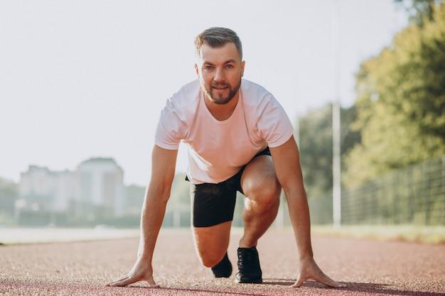 Atleta masculino correndo no estádio pela manhã