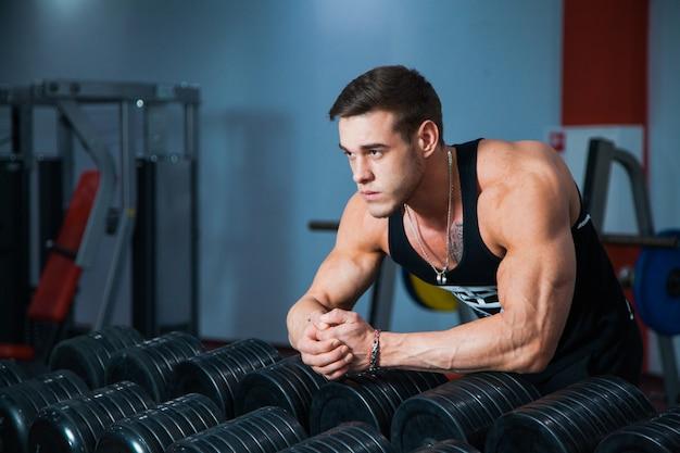 Atleta masculino em forma se preparando para o treino com halteres