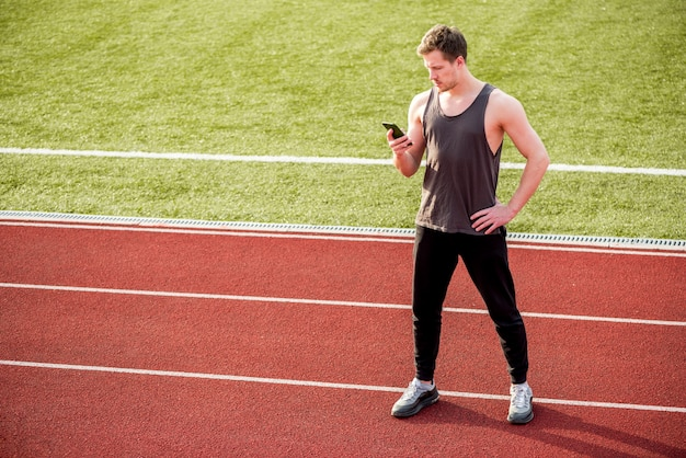 Atleta masculino em pé na pista de corrida usando telefone celular