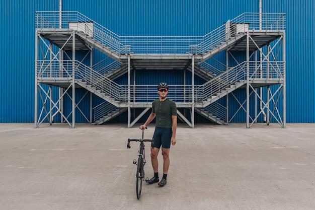Atleta masculino em roupas esportivas em pé com bicicleta na área urbana