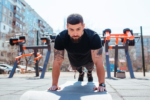 Atleta masculino faz flexões em campo esportivo ao ar livre
