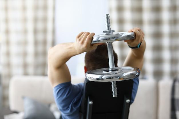 Atleta masculino fazendo esportes em casa com halteres