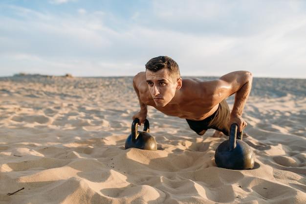 Atleta masculino, fazendo exercícios de flexão com dois kettlebells no deserto em dia de sol. forte motivação no esporte, treinamento de força ao ar livre