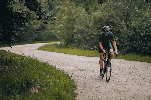 Atleta masculino forte andando de bicicleta em trilha na floresta