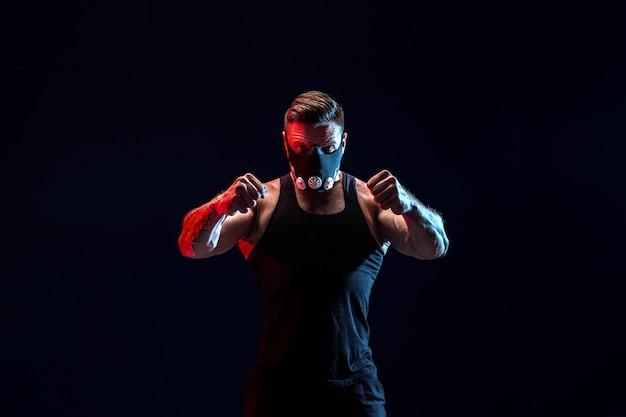 Atleta masculino forte em uma máscara de treinamento preto em uma parede preta