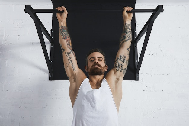 Atleta masculino forte tatuado em camiseta branca sem rótulo sem rótulo mostra movimentos calistênicos perto de pullup clássico pendurado na barra de puxar