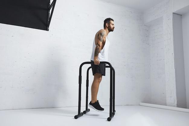 Atleta masculino forte tatuado em camiseta branca sem rótulo sem rótulo mostra movimentos calistênicos segurando a posição nas barras paralelas antes dos mergulhos clássicos, olhando em linha reta