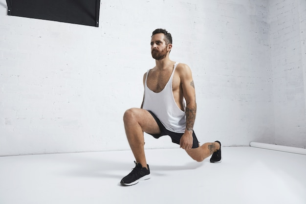 Atleta masculino forte tatuado em camiseta regata branca sem rótulo mostra movimentos calistênicos lunges, olhando de lado