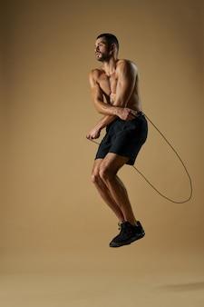 Atleta masculino forte treinando dentro de casa com corda de pular