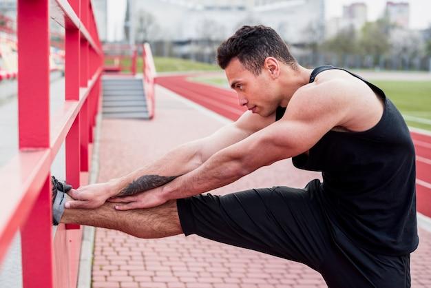 Atleta masculino jovem fitness, esticando a perna no estádio