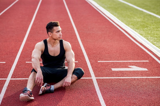 Atleta masculino jovem fitness relaxante na pista de corrida vermelha no estádio