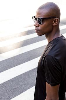 Atleta masculino jovem sério na camisa preta, usando óculos de sol, olhando para longe