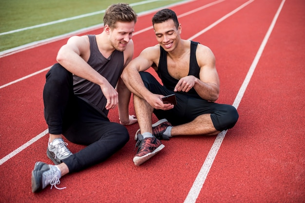 Atleta masculino mostrando algo no celular para seus amigos sentado na pista de corrida