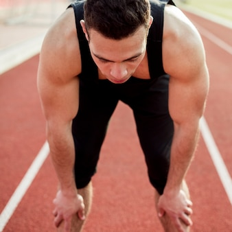 Atleta masculino musculoso em pé na pista de corrida