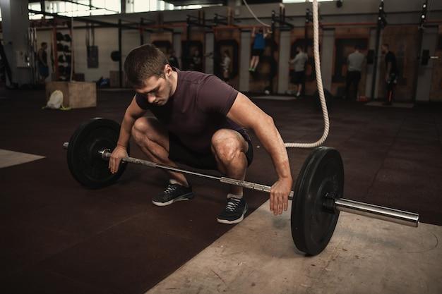 Atleta masculino musculoso fazendo levantamento terra com barra pesada no ginásio cross fit