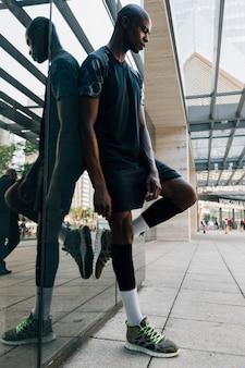 Atleta masculino novo africano contemplado que inclina-se no espelho reflexivo em fora