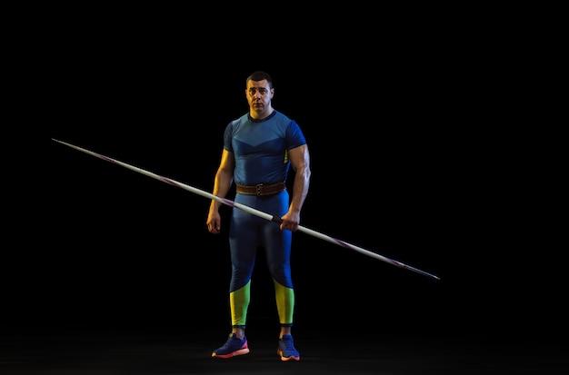 Atleta masculino praticando lançamento de dardo no escuro