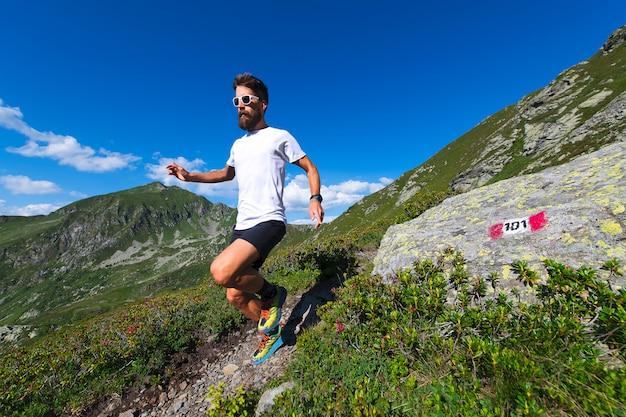 Atleta masculino praticando montanha correndo em uma trilha marcada pelos alpes oróbicos