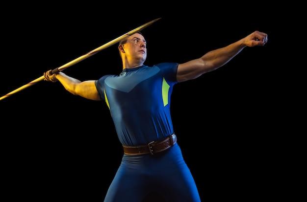 Atleta masculino praticando no lançamento de dardo isolado no estúdio preto em luz de néon