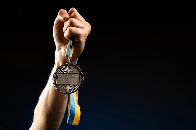 Atleta masculino segurando uma medalha