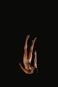Atleta masculino voando de cabeça para baixo