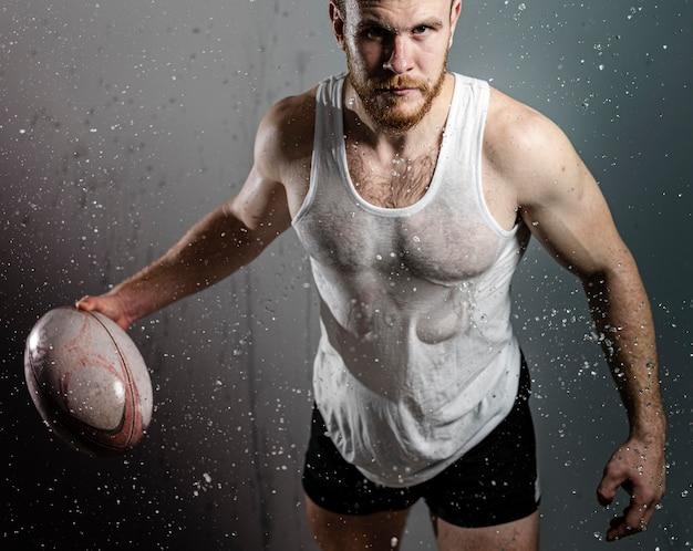 Atleta molhado jogador de rúgbi segurando a bola