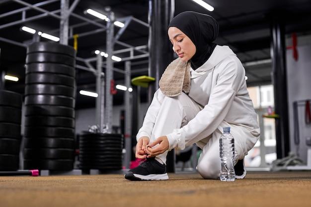 Atleta muçulmana amarra o cadarço do tênis antes dos exercícios esportivos, vai fazer exercícios na academia, usa hijab esportivo branco, jovem árabe leva estilo de vida saudável