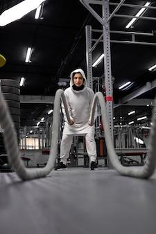 Atleta muçulmana de cross fit feminina em hijab malhando com cordas pesadas olhando determinad e concentrada treinamento funcional atletismo fitness atividade esportiva fortalecimento da confiança