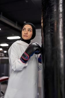 Atleta muçulmana envolvida em kickboxing, olhando para cima em pé ao lado de um enorme saco de pancadas, usando um hijab. jovem forte boxeador árabe treinando duro.