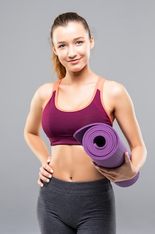 Atleta muito jovem segurando um tapete de fitness enquanto fica isolada