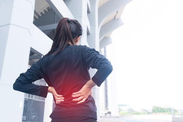 Atleta mulher corredora com lesão de dor nas costas durante o treinamento com apoio de mão nas costas. overtrained ferido.