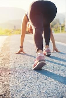 Atleta, mulher, em, corrija começar, pose, ligado, rua, estrada, pôr do sol, montanha, fundo