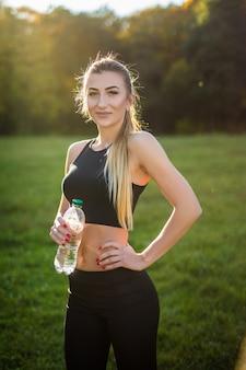 Atleta mulher faz uma pausa, ela bebendo água, em uma corrida em um dia quente