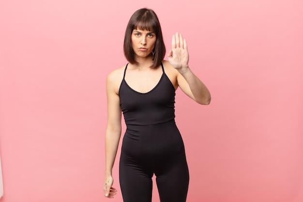 Atleta mulher parecendo séria, severa, descontente e irritada mostrando a palma da mão aberta fazendo gesto de parada