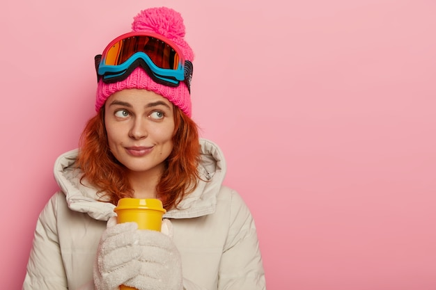 Atleta mulher pensativa, veste agasalhos quentes, bebe café para viagem, concentrada, modelos contra a parede rosa do estúdio