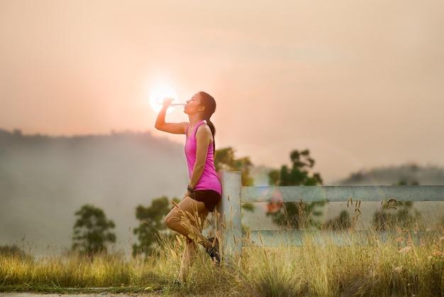 Atleta mulheres bebendo água depois de correr no pôr do sol do céu