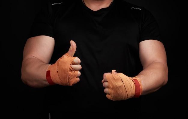 Atleta musculoso de uniforme preto mostra as palmas das mãos envoltas em bandagem esportiva têxtil laranja