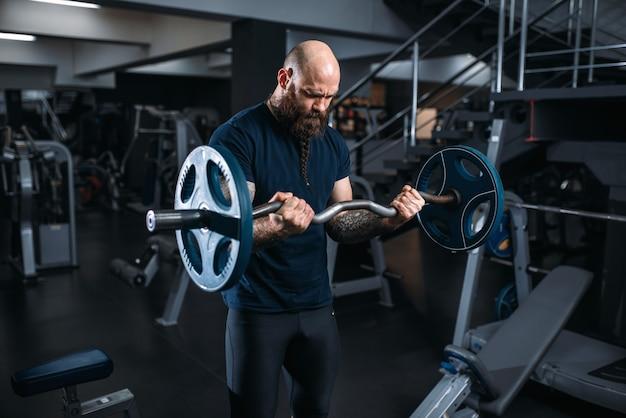Atleta musculoso em roupas esportivas, fazendo exercícios com barra, treinando no ginásio.