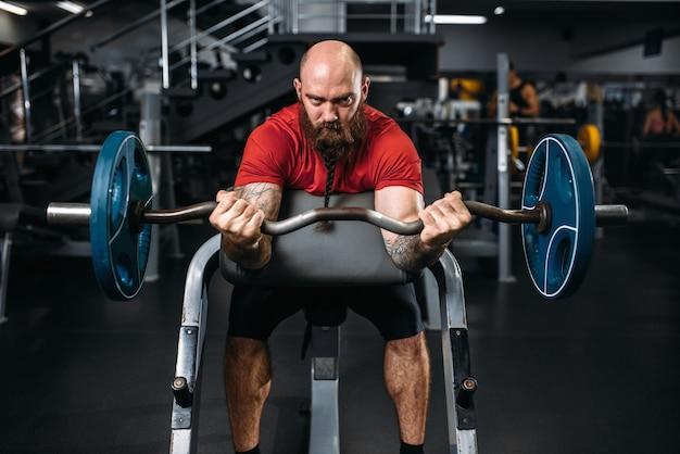 Atleta musculoso fazendo exercício com peso no ginásio.