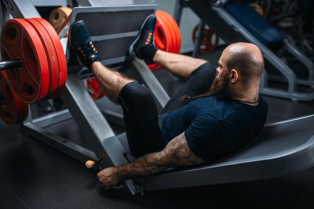 Atleta musculoso na máquina de exercícios com barra