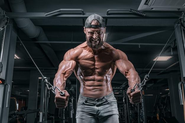 Atleta musculoso treinando em um crossover no ginásio. bombeando o torso. conceito de fitness e musculação.