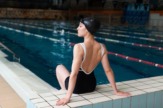 Atleta na borda da piscina tacada completa