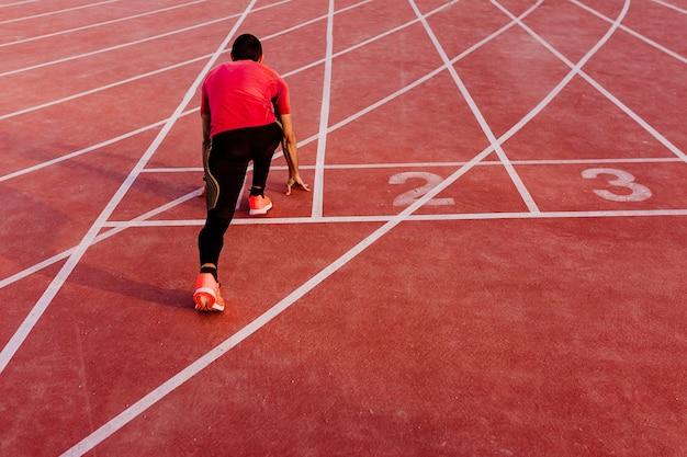 Atleta na linha de pistas de corrida no estádio